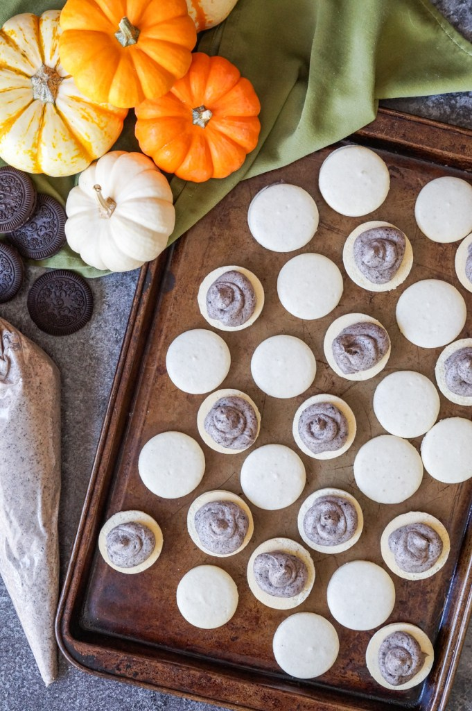 Mummy Macarons on a brown baking sheet with cookies and cream filling and orange/white pumpkins on the side.