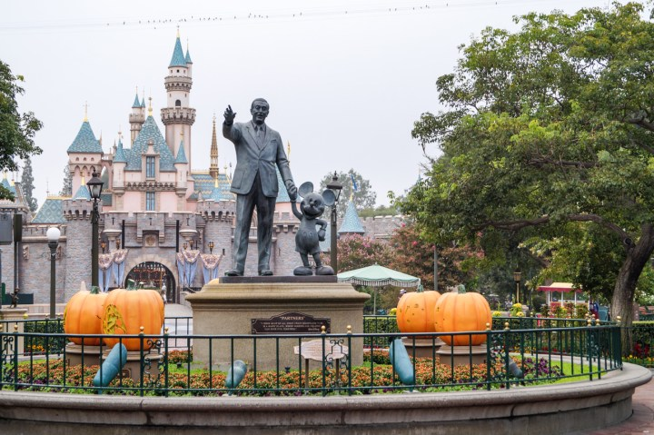 Statue of Walt Disney holding Mickey Mouse's hand in front of the castle at Disneyland