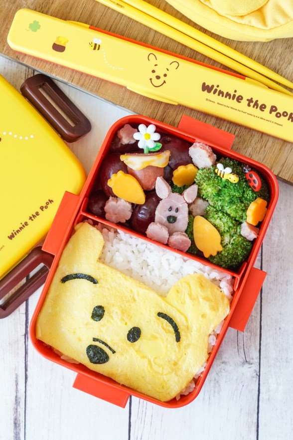 Aerial view of Winnie the Pooh Bento Box with rice, Winnie the Pooh egg crepe, ham-shaped piglet, hunny pot hot dog, cheese carrots and flowers, grapes, and broccoli next to a pair of yellow chopsticks with a Winnie the Pooh yellow chopstick holder.