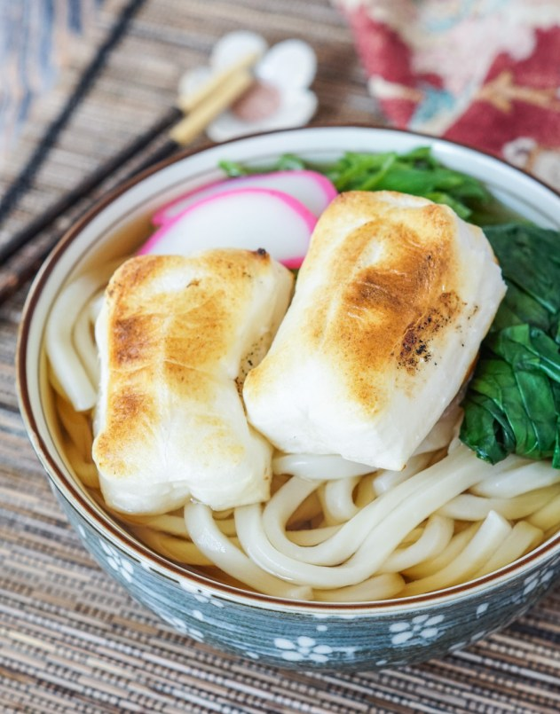Close up of Chikara Udon (Japanese Power Udon) in a bowl with toasted mochi, fish cakes, and spinach.