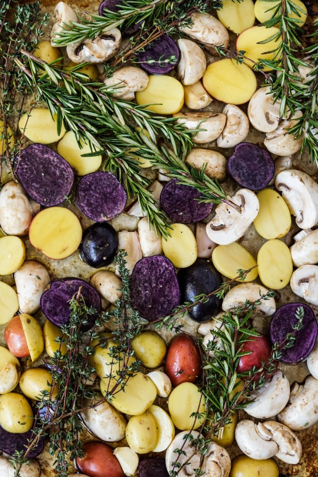 Aerial view of purple and yellow baby potatoes, rosemary sprigs, and mushrooms on a baking sheet.