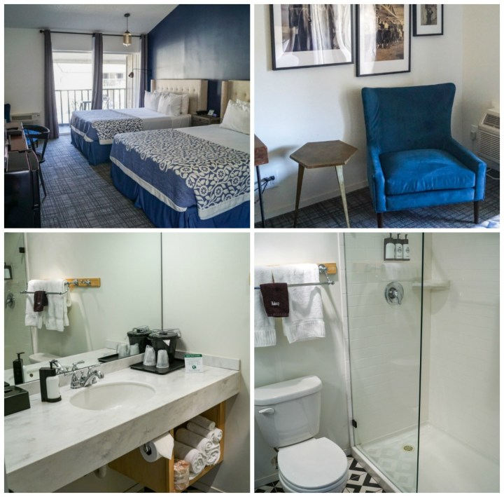 Room at the Sideways Inn with bathroom, standing shower, blue armchair, and blue/white beds
