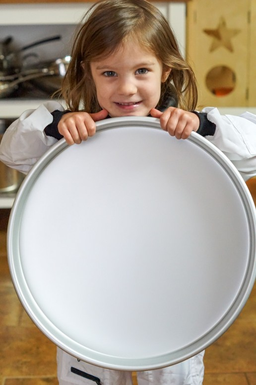 Girl holding up the large 15 inch round silver baking dish.