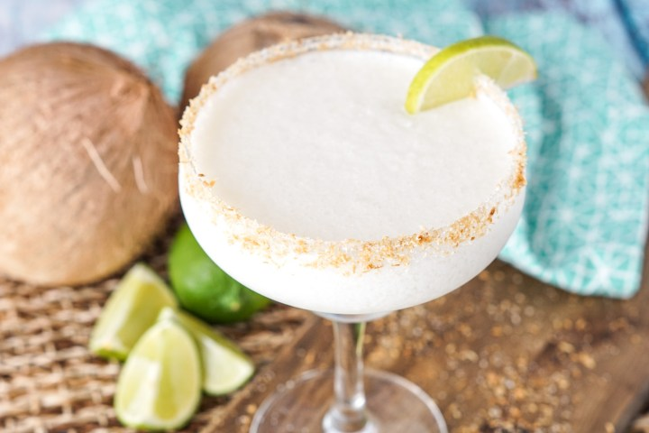 Frozen Coconut Margarita in a tall, wide glass with coconut rim, lime wedge, and coconuts in the background
