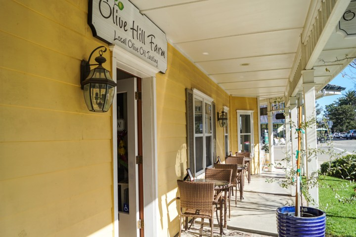 Entrance to Olive Hill Farm- Local Olive Oil Tasting yellow building. Tables and chairs lined against the wall.