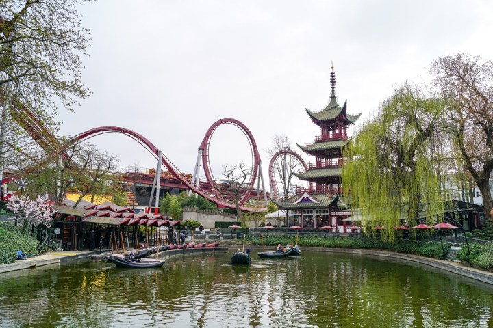 Pond in Tivoli Gardens with roller coaster in background.