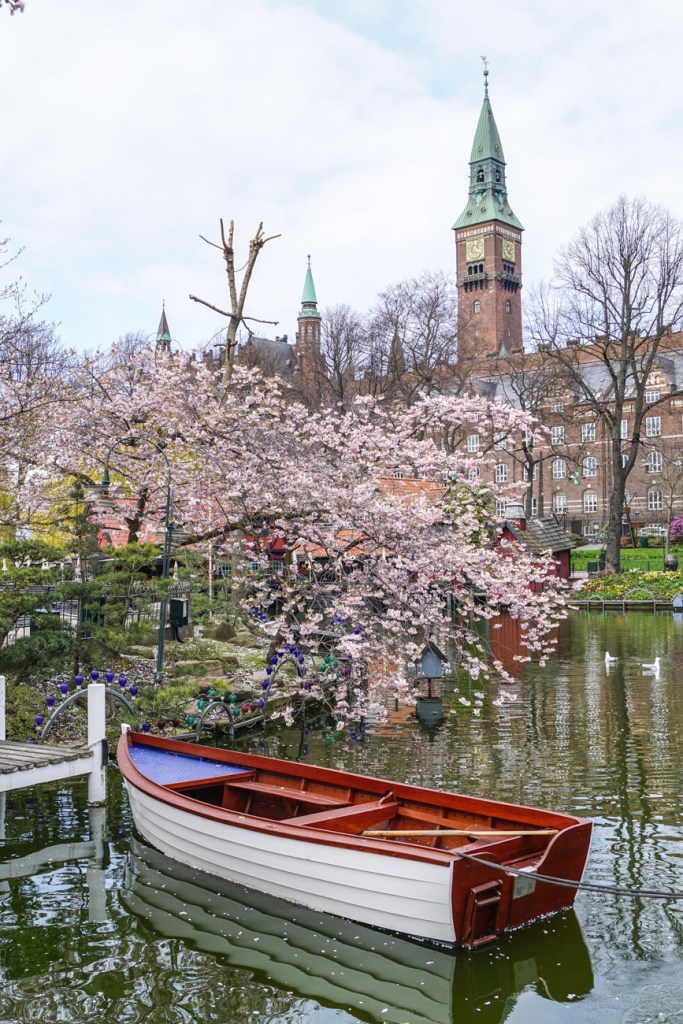 Cherry blossoms over a boat in the water at Tivoli Gardens.