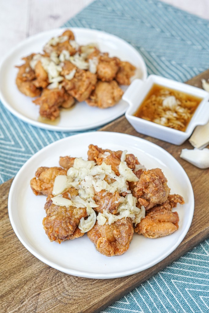 Garlic Fried Chicken on two white plates next to a small white bowl with garlic sauce