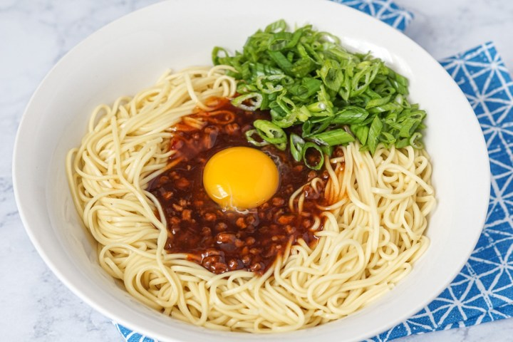 Taiwan Mix Soba Sauce over a bed of thin egg noodles and topped with sliced green onions in a white bowl.