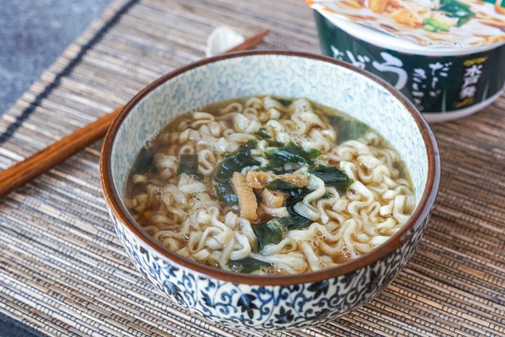 Udon Dappe thick udon noodles with a bonito broth in a white and blue bowl with a brown rim.