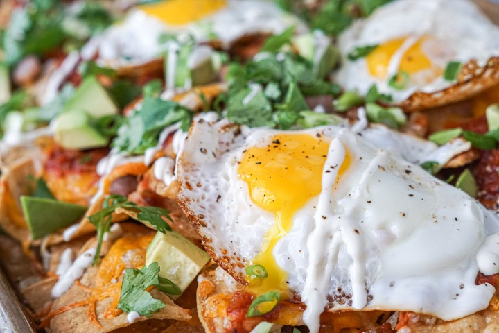 Breakfast Nachos on a baking sheet with fried egg and sour cream