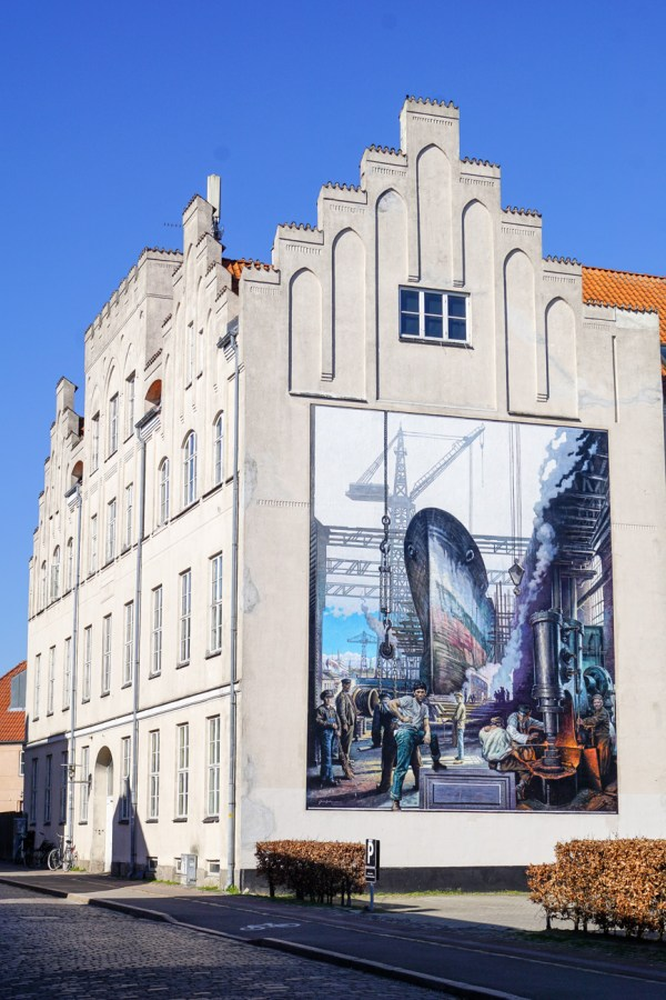 Mural on the side of a building in Helsingør of a large boat at port with people working.