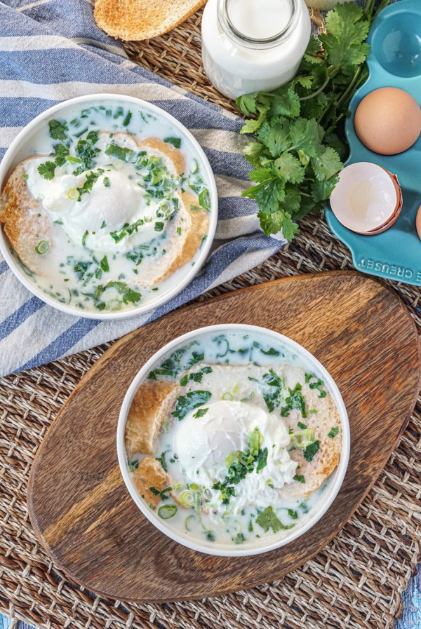 Aerial view of Changua (Colombian Egg and Milk Soup) with cilantro and eggs in two white bowls.