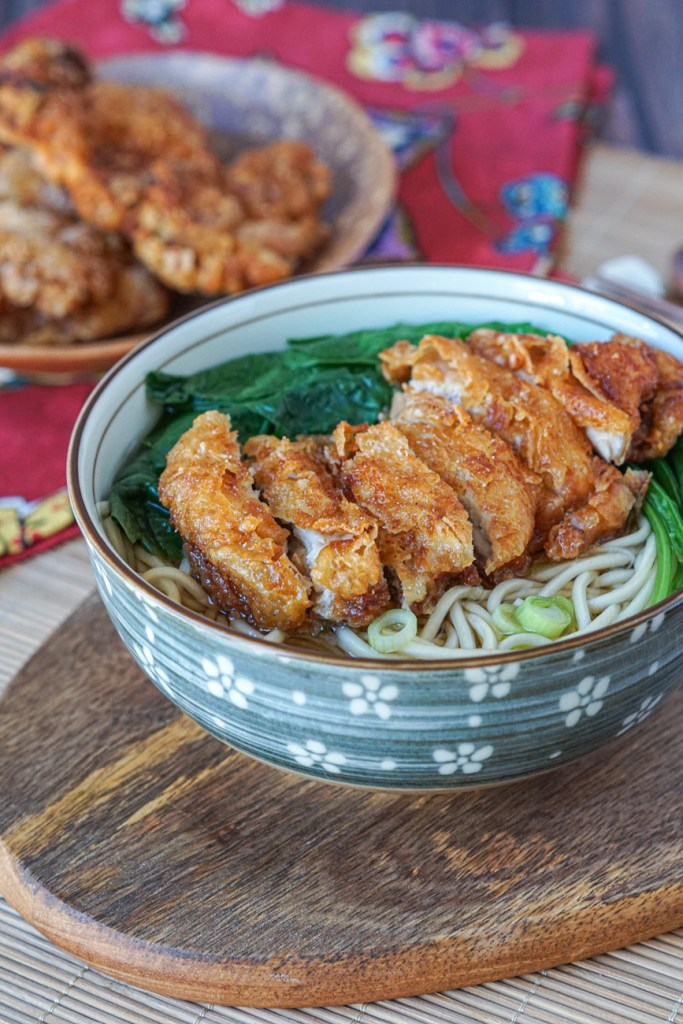 Fried Chicken Soup Noodles with Spinach in a bowl on a wooden board.