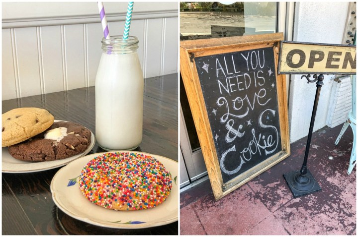 "Sprinkles, rocky road, and chocolate chip cookies on two plates and a jar of milk at Milk Jar Cookies. Sign in front stating, ""All You Need Is Love & Cookies, Open"""