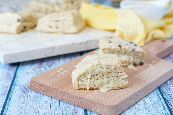Irish Cream Scones drizzled with an Irish Cream glaze on a wooden board with more in the background next to a yellow towel.