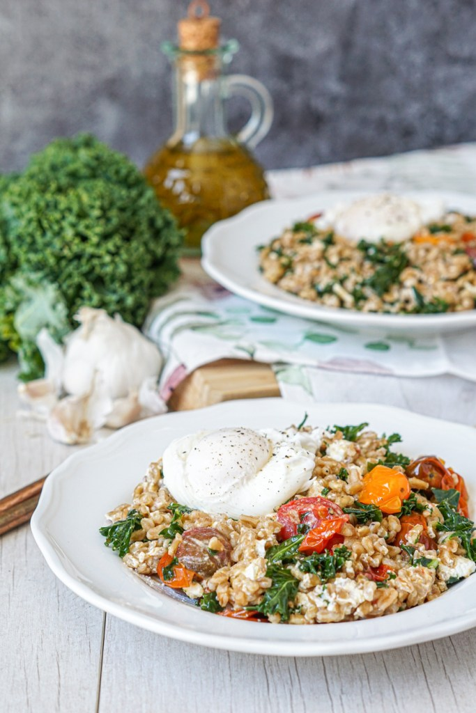 Farro Salad with Kale and Roasted Tomatoes on a white plate with garlic, kale, and olive oil in the background.