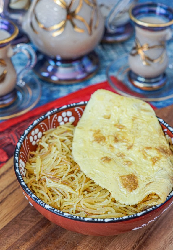 Balaleet (Emirati Sweet Vermicelli and Egg Omelet) in a red bowl with an Arabic tea set in the background with Karak Chai.