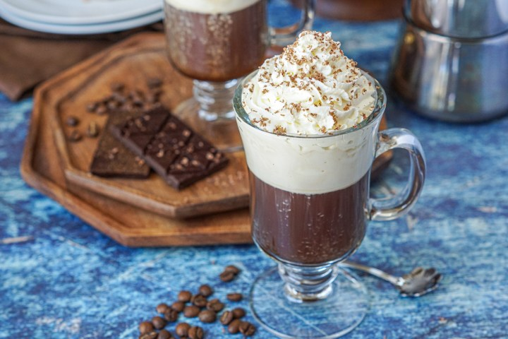 Einspänner (Viennese Coffee with Whipped Cream) in a glass with a handle next to coffee beans with a chocolate bar in the background.