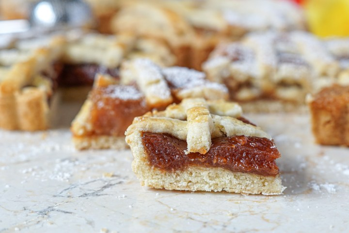 Slice of Pasta Frola (Argentinian Lattice Tart) filled with Dulce de Membrillo (Quince Paste) with tarts in the background covered in powdered sugar.