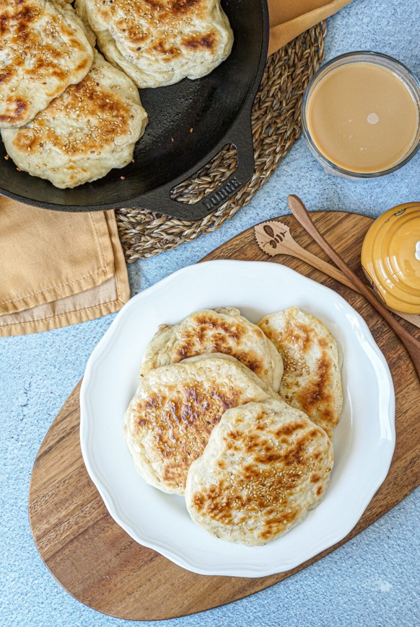 Aerial view of three Mkatra Foutra (Sesame Coconut Flatbreads) on a white plate and three more in a cast iron skillet next to coffee and a beehive-shaped honey pot.