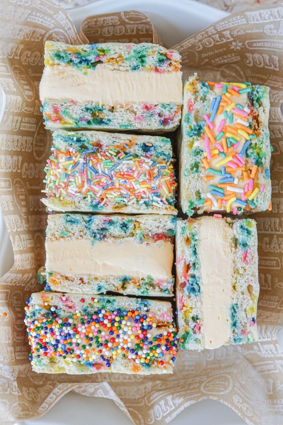 Aerial view of six Funfetti Ice Cream Sandwiches in a white baking dish with a tan liner. Three plain and three covered in sprinkles around the ice cream.