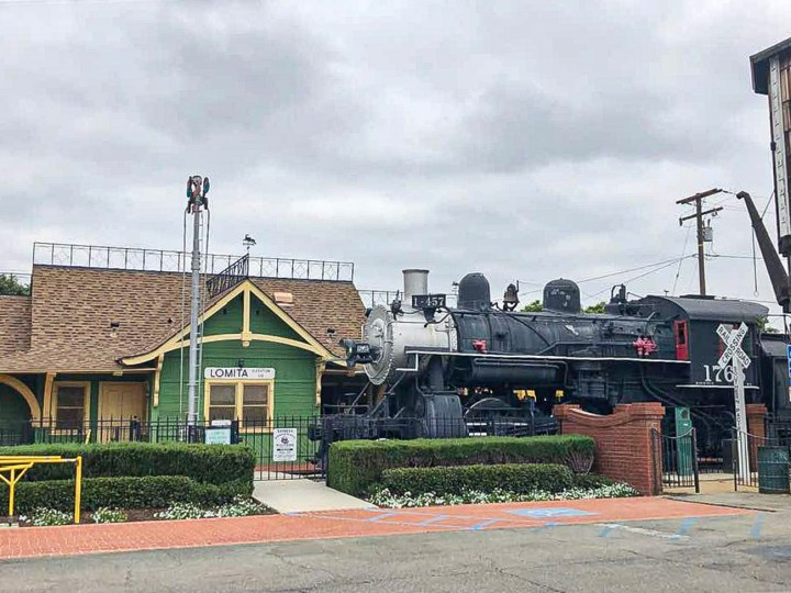 Entrance to the Lomita Railroad Museum with a green building with yellow trim and black train in front.