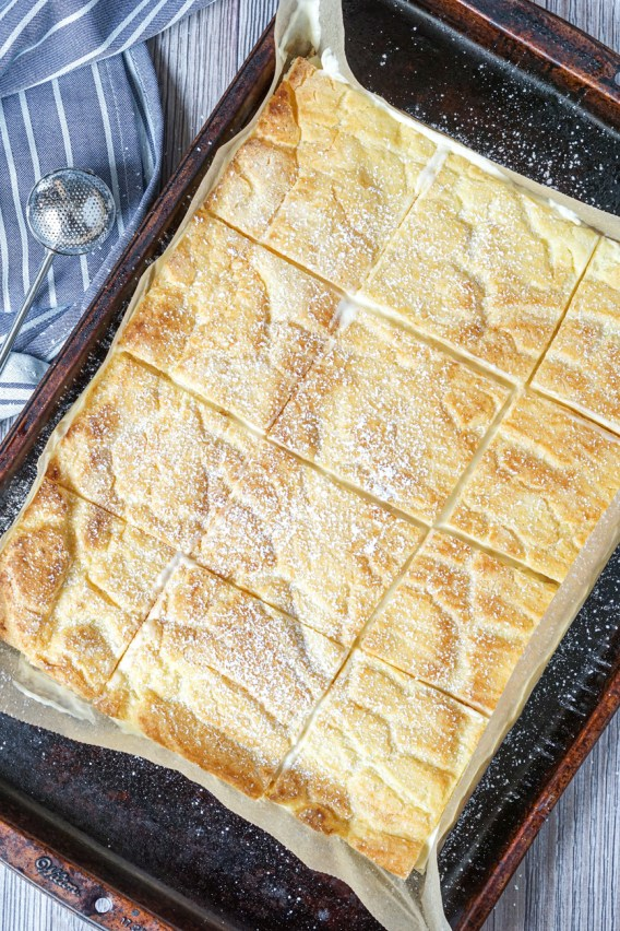 Aerial view of Karpatka (Polish Carpathian Cream Cake) cut into 12 squares on a brown baking sheet next to a grey and white striped towel and a sugar duster.