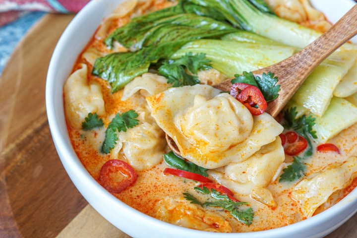 Close up of Red Curry Chicken Wonton Soup in a white bowl with one wonton in a wooden spoon with cilantro and sliced red chilies.