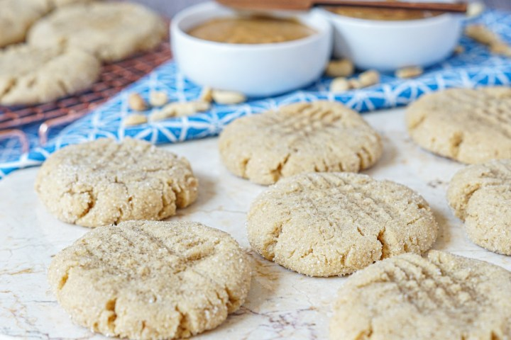 Seven Peanut Butter Cookies on a marble board with peanut butter in two white bowls in the background on a blue and white towel with scattered peanuts.