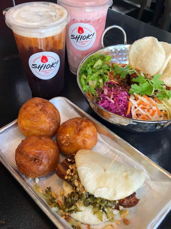 Buns, tea, strawberry drink, and vegetable bowl from Shiok.