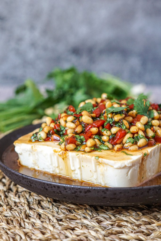 Side view of Silken Tofu with Pine Nuts and Pickled Chiles on a brown plate with green onions and cilantro in the background.