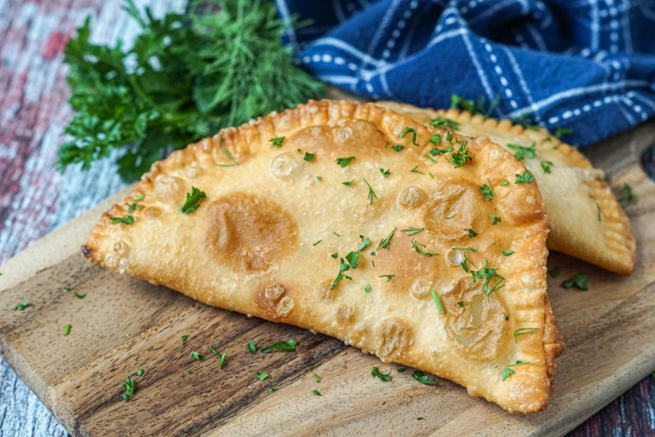 Two Cheboureki (Beef and Garlic Meat Pies) on a wooden board next to fresh parsley, dill, and a blue towel.
