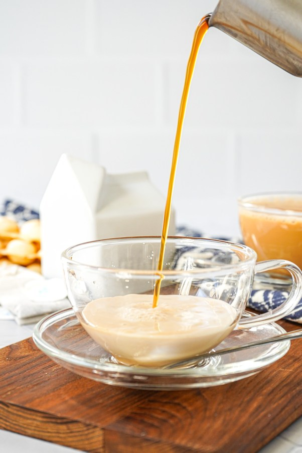 Pouring Hong Kong-Style Milk Tea into a clear tea cup.
