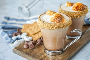 S'mores Latte in two clear glasses and topped with toasted marshmallows.