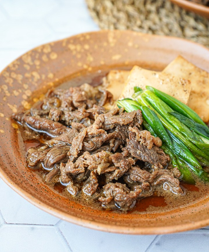 Simmered Beef and Tofu with green onions on a brown plate.