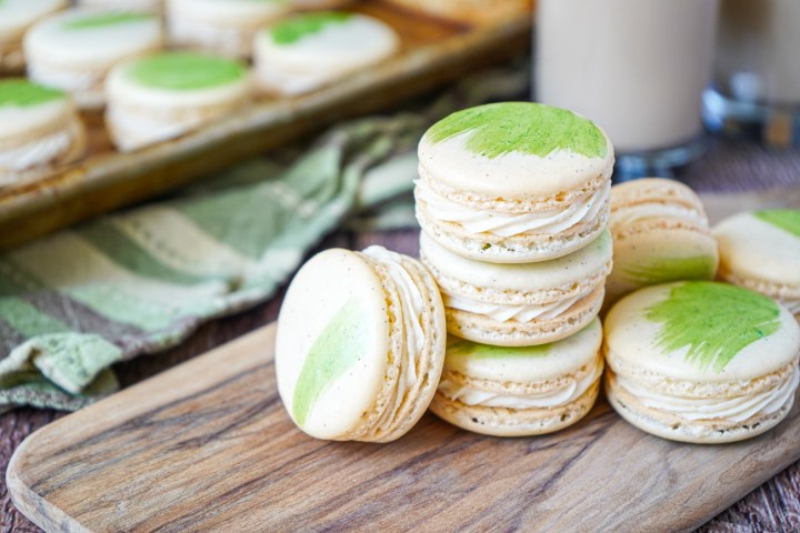 Stacked Irish Cream Macarons on a wooden board with more in the background on a baking sheet.