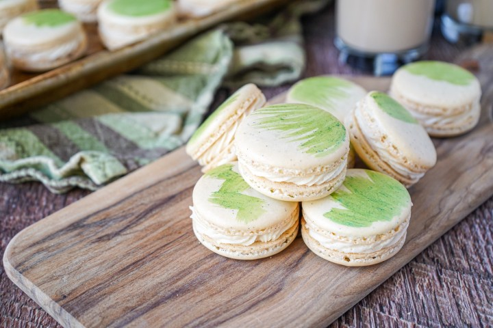 Eight Irish Cream Macarons on a wooden board.