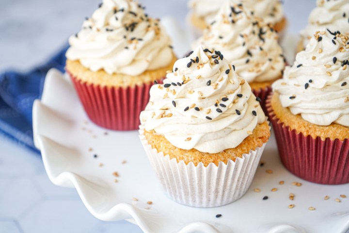 Six Salted Tahini Cupcakes on a white platter and topped with sesame seeds.