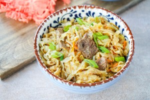 Tsuivan (Mongolian Noodles with Meat and Vegetables) in a blue and brown bowl.