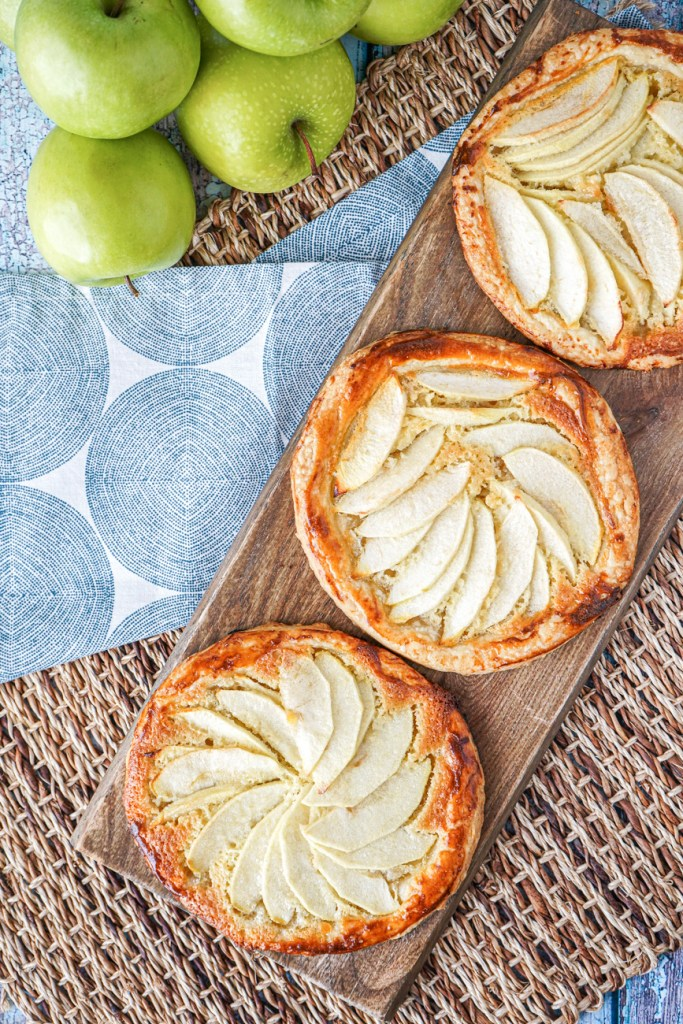 Aerial view of three Apple Tarts with Almond Frangipane on a wooden board next to green apples.