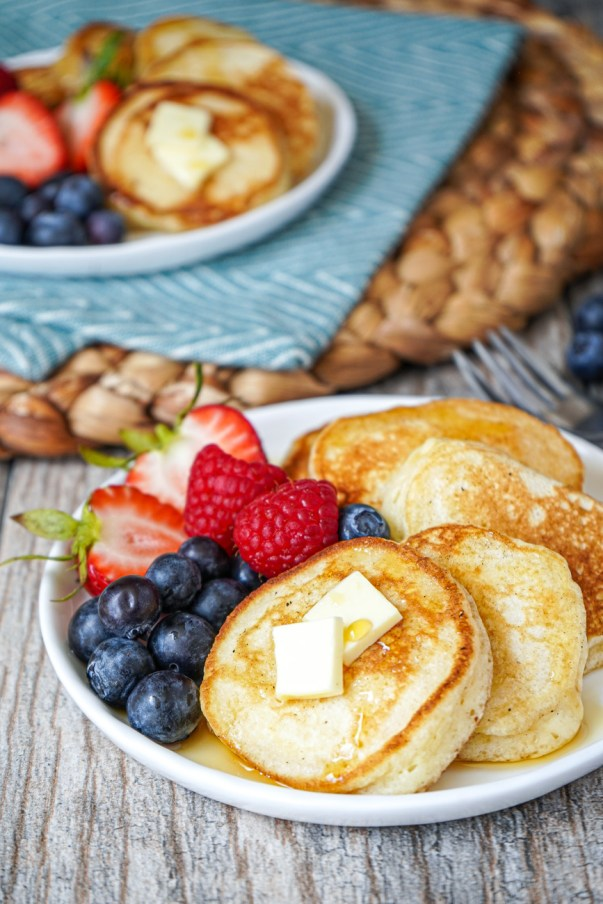 Side view of Silver Dollar Pancakes on two white plates with fresh berries and butter.