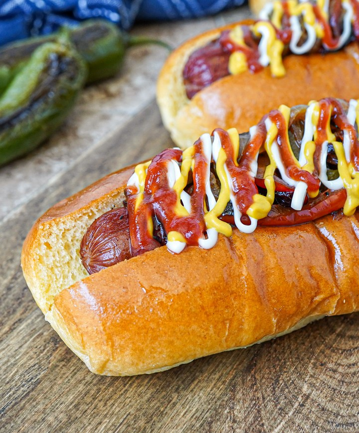Bacon Wrapped Hot Dogs on a wooden board with two jalapeños in background.