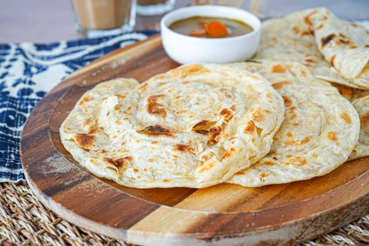 Four Roti Canai (Malaysian-Style Paratha Roti) on a wooden board with a bowl of curry.