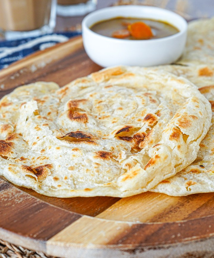 Roti Canai on a wooden board with a white bowl of curry.