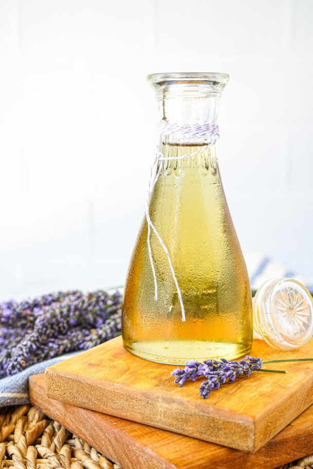 Side view of Homemade Lavender Syrup in a glass jar with fresh lavender in the background.