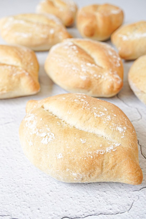 Close up of Papo Secos (Portuguese Crusty Rolls) on a chipped white background.