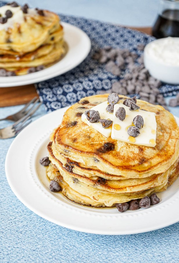 Two stacks of Chocolate Chip Ricotta Pancakes on white plates with butter and chocolate chips.