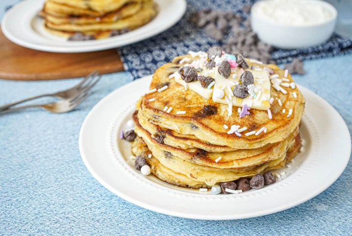 A stack of Chocolate Chip Ricotta Pancakes on a white plate topped with butter and sprinkles.