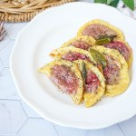 Casunziei All'Ampezzana (Beet Filled Pasta with Poppy Seeds) on a white plate topped with sage.